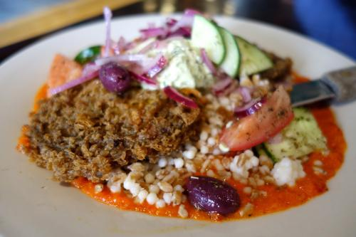Photo of the Muse: two generous pieces of eggplant fried in falafel batter, couscous farro salad, red pepper pesto, Greek yogurt tahini and xoriatiki salad.