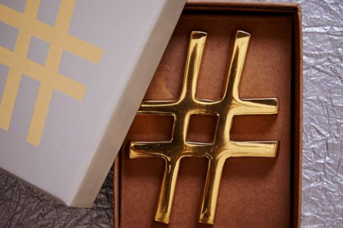 Photo of West Elm brass hashtag paper weight.